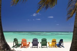 group of six empty colorful chairs between coconut palm trees at a tropical beach in the Caribbean