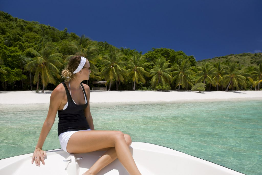 young woman on boat approaching white sand beach with palm trees in the British Virgin Islands