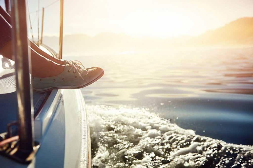 Shoes dangling over the side of a sailing yacht