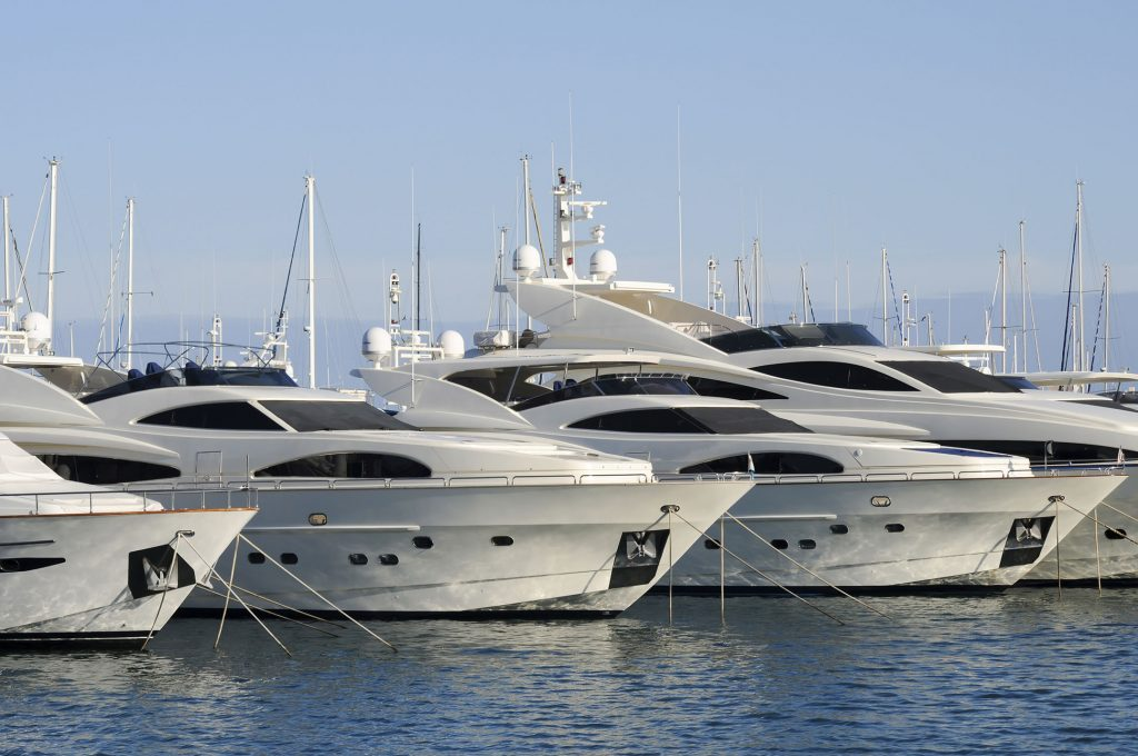 Group of luxury power yachts at a dock in the tropics.